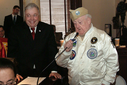 """World War II Veteran and former private in Easy Company, Edward """"Babe"""" Heffron, addresses the State Senate while Senate Military and Veterans Affairs Committee Chairman, Senator Jim Beach, D-Camden, looks on. Heffron and his platoon were the subject of the book and 10-part HBO miniseries, Band of Brothers."""